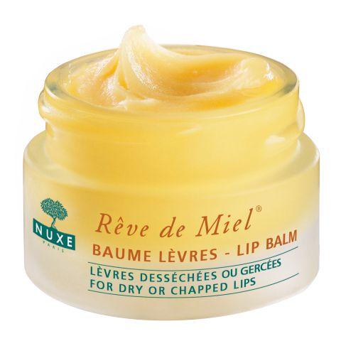 Нюкс Рэв Де Мьель Бальзам для губ ультрапитательный  (Банка 15 мл)Уход за губами<br>Nuxe Reve de Miel Lip balm (Нюкс Рэв Де Мьель Бальзам для губ ультрапитательный) для сухой, чувствительной кожи.<br>Бальзам Nuxe Reve de Miel Lip balm с высокой концентрацией смягчающих, увлажняющих и заживляющих компонентов – это средство, которое рекомендуется всегда иметь под рукой. Он моментально восстанавливает комфорт и делает нежными даже очень сухие и растрескавшиеся губы. Не липкая и не жирная защитная пленка из натуральных растительных восков обеспечивает защиту от вредных внешних воздействий. Берите с собой этот чудесный бальзам для профилактики сухости и повреждений губ, когда идете на прогулку с ребенком (начиная с трех лет), купаетесь и загораете, участвуете в турпоходах. Активные компоненты:<br>воски природного происхождения (пчелиный и канделильский) образуют на губах защитную пленку, придают им блеск;<br>мед акации заживляет ранки и трещины, питает и увлажняет, насыщает кожу витаминами и микроэлементами;<br>масла карите, сладкого миндаля и мускатной розы смягчают, питают, увлажняют, ускоряют лечение трещин;<br>лецитин и аллантоин успокаивают и смягчают кожу, ускоряют регенерацию клеток;<br>масла грейпфрута и лимона – мощные антисептики;<br>диметикон делает кожу губ очень мягкой и гладкой, создает на ее поверхности «дышащую» защитную пленку;<br>каприловые триглицериды повышают эластичность кожи, защищают ее от вредных внешних воздействий;<br>экстракт цветков календулы успокаивает, заживляет кожу и активизирует ее защитные функции, стимулирует обновление клеток, уничтожает микроорганизмы и бактерии;<br>токоферол восстанавливает кожу, блокирует свободные радикалы, защищает от УФ-излучения.<br><br>Объем мл: 15<br>Тип кожи: всех типов, сухой, чувствительной